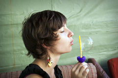 Young woman blowing soap balloons Royalty Free Stock Image