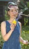 Young woman blowing soap bubbles. Portrait of young woman blowing soap bubbles Stock Image
