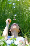Young woman blowing soap bubbles Royalty Free Stock Photos