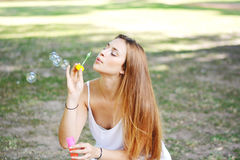 Young woman blowing soap bubbles in the air. Stock Image