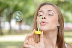 Young woman blowing soap bubbles in the air. Royalty Free Stock Photography