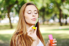 Young woman blowing soap bubbles in the air. Royalty Free Stock Photo