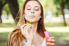 Young woman blowing soap bubbles in the air. Royalty Free Stock Image
