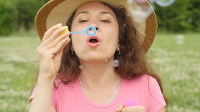 Young woman blowing soap bubbles in a park. Beautiful woman blowing soap bubbles in a park stock footage