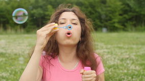 Young woman blowing soap bubbles in a park. Beautiful woman blowing soap bubbles in a park stock video