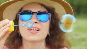 Young woman blowing soap bubbles in a park stock footage