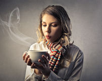 Young woman blowing on a tea cup Royalty Free Stock Photo