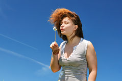 Young woman blowing to dandelion Royalty Free Stock Images