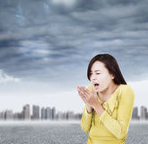 Young woman blowing to warm hands up with black clouds Stock Photos