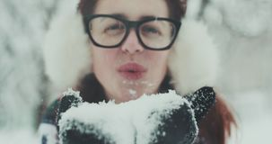 Young woman blowing white snowflakes into camera. Happy girl sending snow kiss on winter day. Playful woman blowing. SLOW MOTION CLOSE UP: Young woman blowing stock video