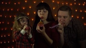 Family together celebrate the holiday. A young woman blows a candle on a cupcake, her husband and daughter blowing in colorful party horns. Family together