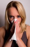 Young woman blows her nose Stock Image