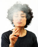 Young woman blows smoke Royalty Free Stock Image