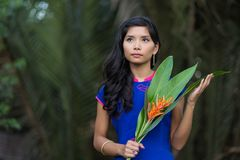 Young Woman in Blue Ao Dai Holding Flowers Stock Images