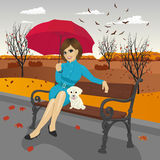 Young woman in blue autumn coat holding red umbrella sitting on a bench Royalty Free Stock Photography