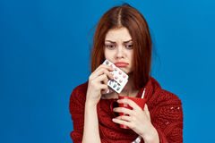 Young woman on a blue background in a scarf holding pills and a mug, flu, sickness, sick, empty space for copying Royalty Free Stock Photo