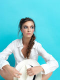 Young woman blue background white hat, shirt Royalty Free Stock Photo