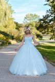 Young woman in blue ball gown in garden. Portrait of young woman in blue ball gown in garden Stock Photo