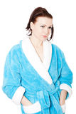 Young woman in blue bathrobe against white Stock Photography