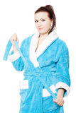 Young woman in blue bathrobe ties waistband Royalty Free Stock Photo