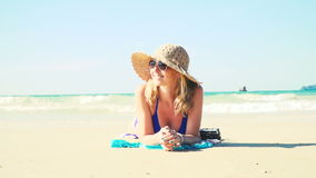 Young woman in blue bikini is lying on the beach with a vintage camera and has a sun hat on stock video footage