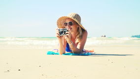 Young woman in blue bikini is lying on the beach with a vintage camera and has a sun hat on stock video