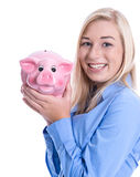 Young woman in a blue blouse isolated with a pink piggy bank Stock Image