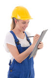 Young woman in blue builder uniform writing something on clipboa Royalty Free Stock Photo