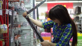 A young woman chooses a large iron ruler with an angle in the supermarket. A young woman in a blue checkered shirt chooses and buys a large iron ruler with an stock footage