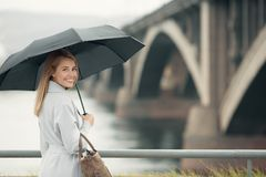 Young woman in blue coat holding umbrella. Autumn city background Royalty Free Stock Image