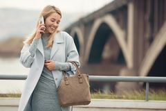 Young woman in blue coat talking phone. Stock Photos