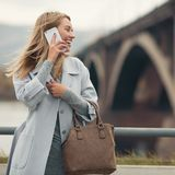 Young woman in blue coat talking phone. Royalty Free Stock Images