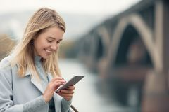 Young woman in blue coat using smartphone. Royalty Free Stock Image