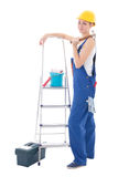 Young woman in blue coveralls with builder's tools and ladder is Royalty Free Stock Photography