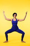 Young woman in blue doing yoga asana on yellow Stock Photography
