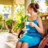Young woman in blue dress enjoying a cup of beverage Royalty Free Stock Images