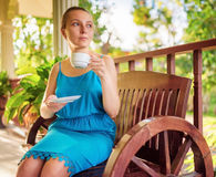 Young woman in blue dress enjoying a cup of beverage Stock Photo