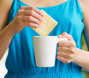 Young woman in blue dress enjoying a mug of beverage Stock Photo