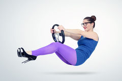 Young woman in blue dress and glasses with a car steering wheel. Lady driver concept Stock Photo