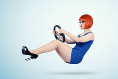 Young woman in blue dress and glasses drives a car with steering wheel Stock Image