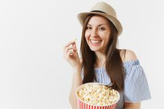 Young woman in blue dress, hat watching movie film holding eating popcorn from bucket isolated on white background stock image
