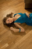 Young woman in a blue dress lays on a parquet stock images
