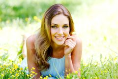 Young woman in blue dress lying on grass Stock Image