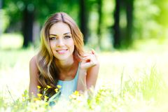 Young woman in blue dress lying on grass Royalty Free Stock Images