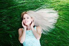 Young woman in blue dress lying on grass Royalty Free Stock Photography