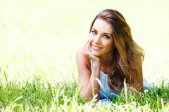 Young woman in blue dress lying on grass Stock Images
