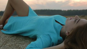 Young woman in blue dress lying sexy on a stack of hay. stock video footage