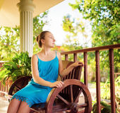 Young woman in blue dress relaxing in house terrace. Stock Photography