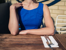 Young woman in blue dress at restaurant table Stock Image