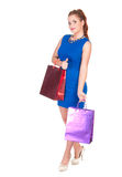 Young woman in blue dress with shopping bags Stock Image